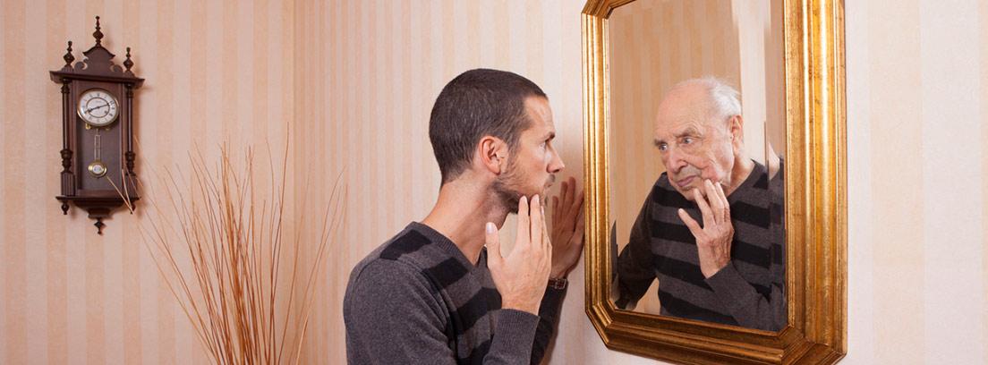 hombre joven mirando su rostro en el espejo de hombre mayor