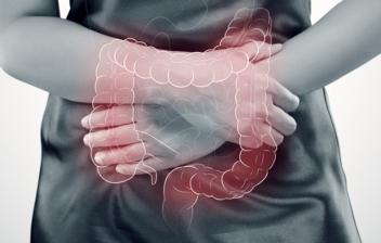 manos de mujer cruzadas sobre el abdomen y dibujo de intestino