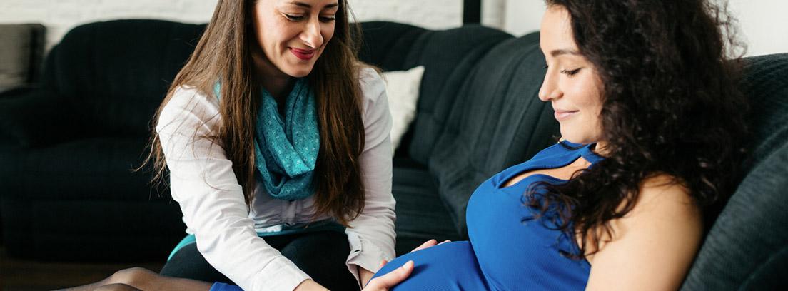 mujer asistiendo a embarazada en casa, ejerciendo el papel de doula o matrona