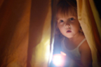 niña detrás de una cortina con una linterna en la mano
