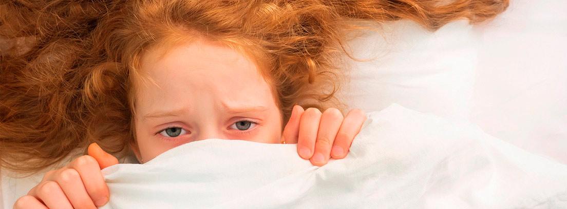 niña pelirroja tapándose la mitad de la cara con una sábana