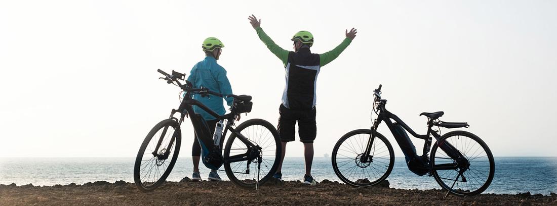 dos personas de espaldas con bicicletas a los lados enfrente del mar