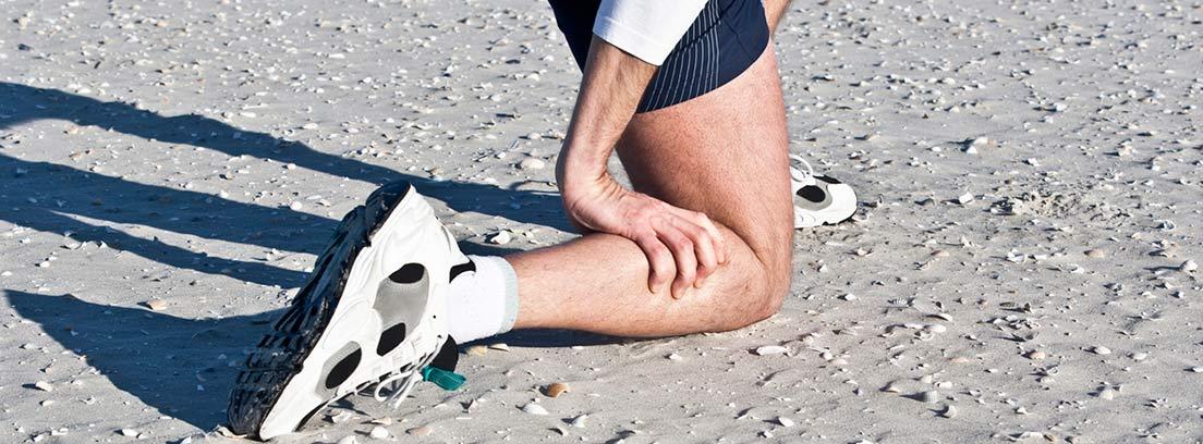 deportista de rodillas con la mano en la pantorrilla