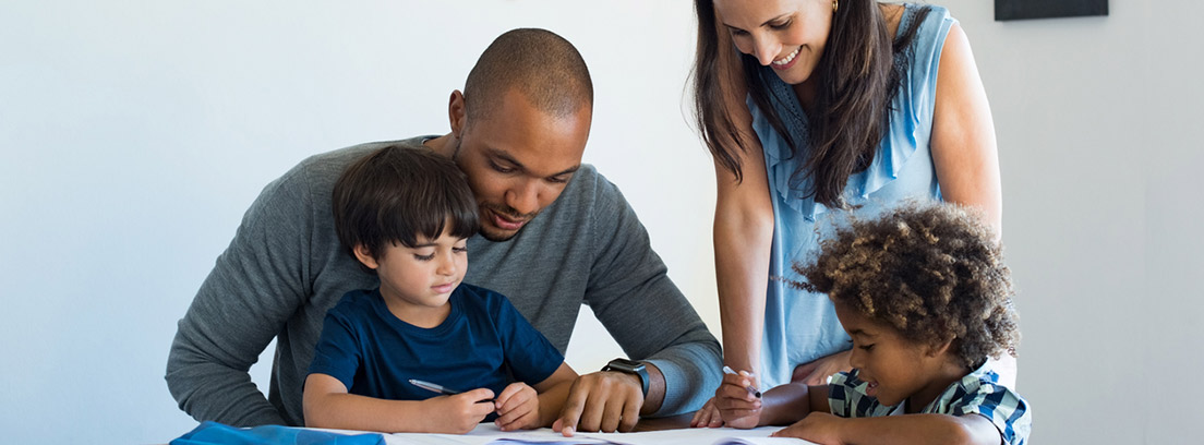 padres ayudando a sus dos hijos a hacer los deberes
