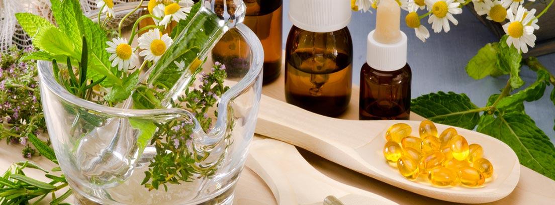 mortero de cristal con planta medicinales, frascos y cápsulas de fitoterapia