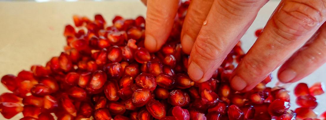 dedos cogiendo granos de granada