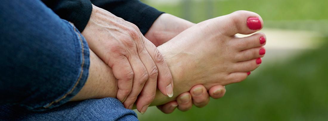 manos cogiéndose un pie con la uñas pintadas de rojo