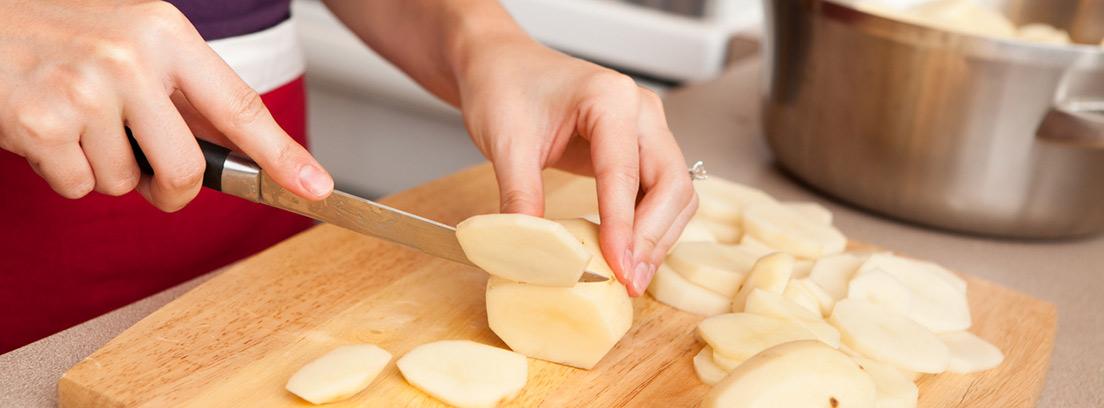 mujer cortando patatas crudas