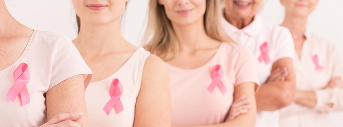mujeres con camisetas rosas y el lazo representación de cáncer de mama