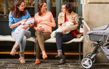 madres con sus bebés en brazos, mujer embarazada sentadas en un banco