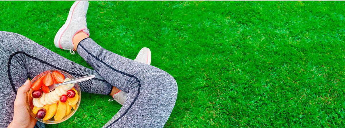 Prepararse para correr: deportista con un bol de frutas y cereales sentada en el cesped