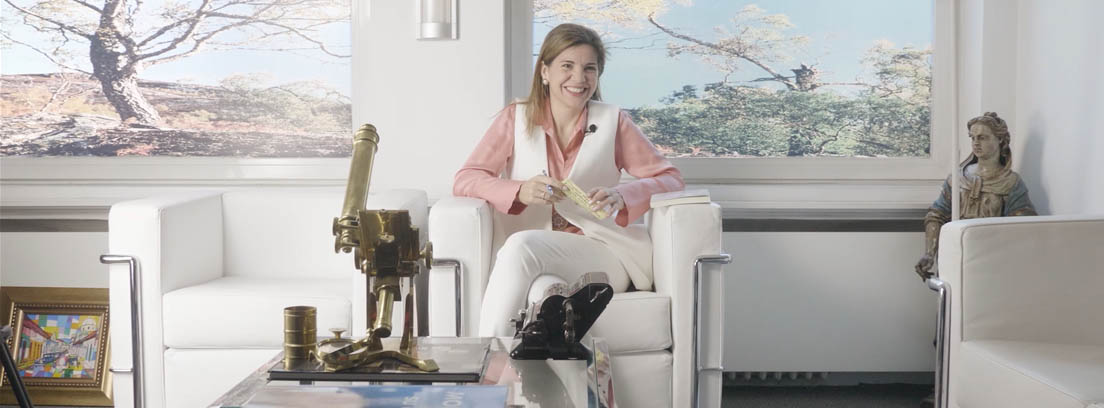 La psiquiatra Marian Rojas-Estapé, con chaleco blanco y camisa rosa sentada en el despacho de la consulta de su padre, el también psiquiatra Enrique Rojas.