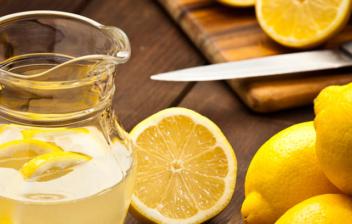 lomones enteros, partidos y una jarra de agua con limón