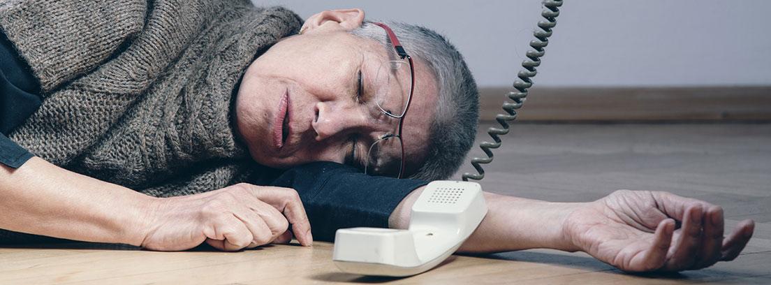 hombre caído en el suelo con el teléfono descolgado