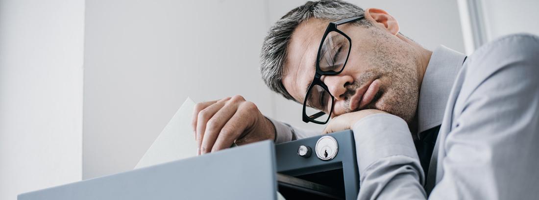 hombre dormido encima de un archivador
