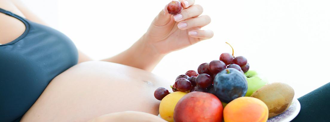 mujer embarazada tumbada con un plato de frutas en una mano y en la otra una uva