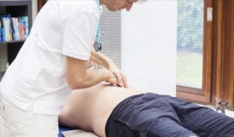Médico comprobando si el paciente tiene o no dolor abdominal.