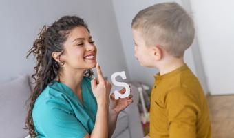 Logopeda enseñando a un niño.