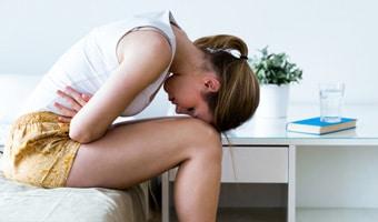mujer con fuerte dolor de estómago