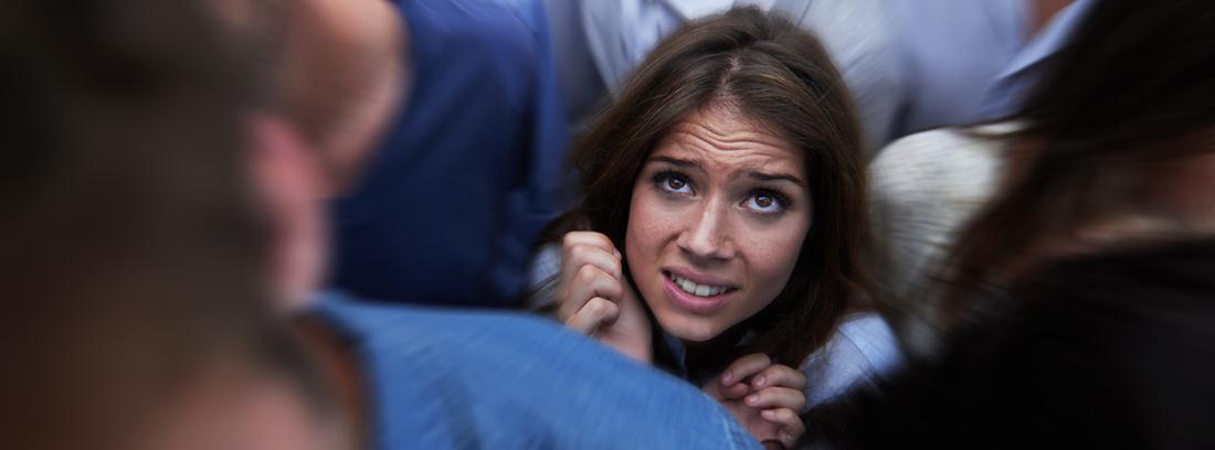 chica con cara de miedo rodeada de multitud