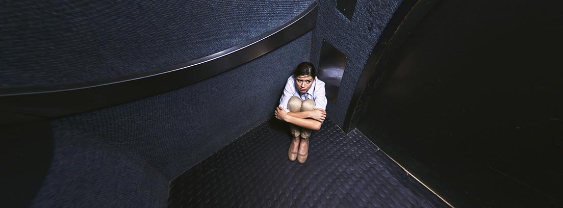chica sentada en el suelo en un rincón del ascensor