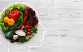 silueta de una cabeza con diferentes alimentos en el cerebro