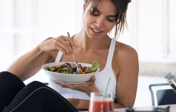 mujer jovén comiendo sola en la cocina