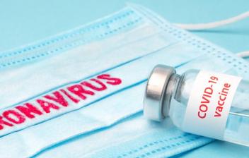 mascarilla con la palabra coronavirus y una vacuna