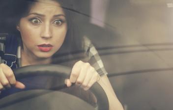 mujer joven al volante con gesto asustado
