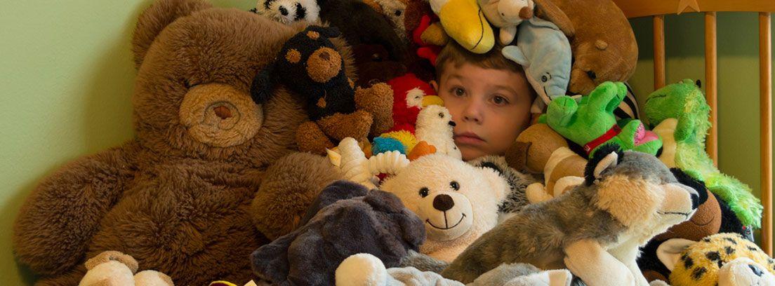niño escondido entre un motón de peluches