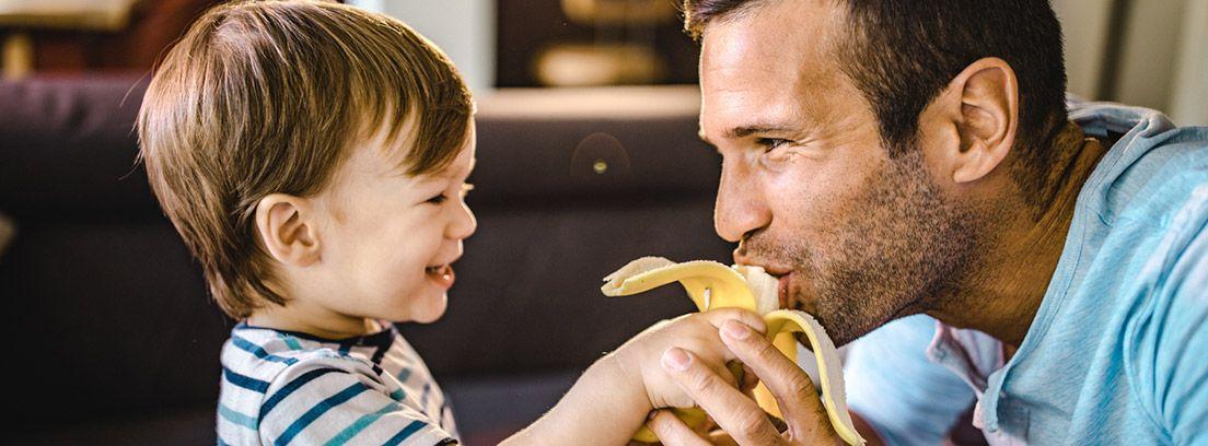 niño dando de comer un plátano a su padre