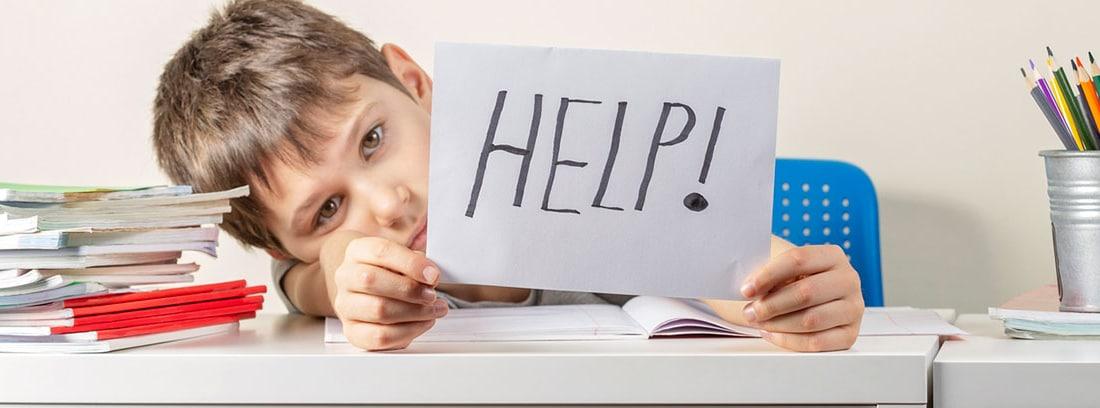 Problemas de aprendizaje en niños: niño medio tumbado sobre una mesa de estudio con una hoja en la mano con la palabra ayuda