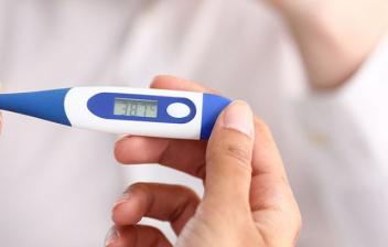 Qué temperatura se considera fiebre: manos cogiendo un termómetro