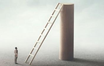 Acrofobia, miedo a las alturas: hombre mirando la altura de una escalera que está apoyada en una columna