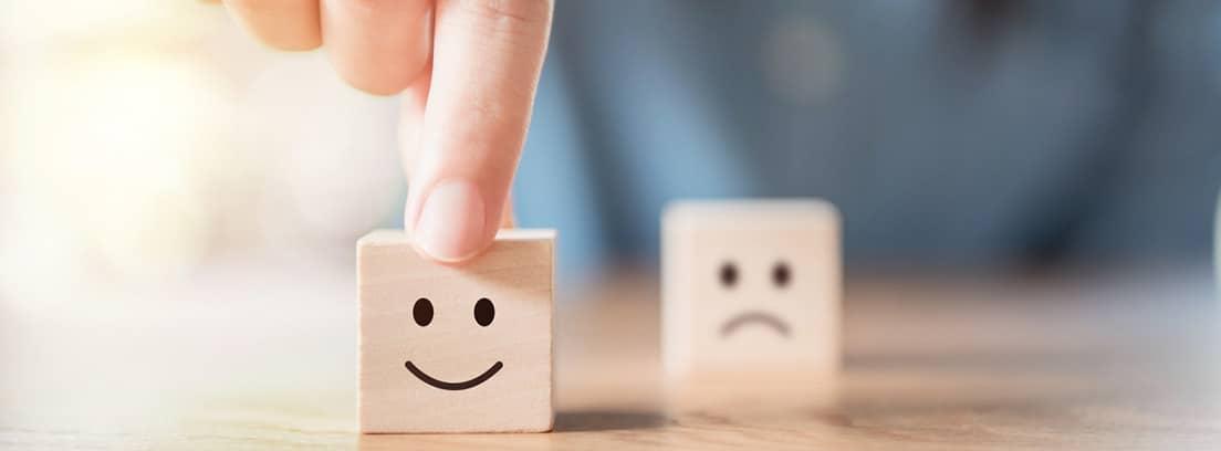 ¿Qué es el positivismo vacío: mano eligiendo cara sonriente y el icono de cara triste borrosa en cubo de madera