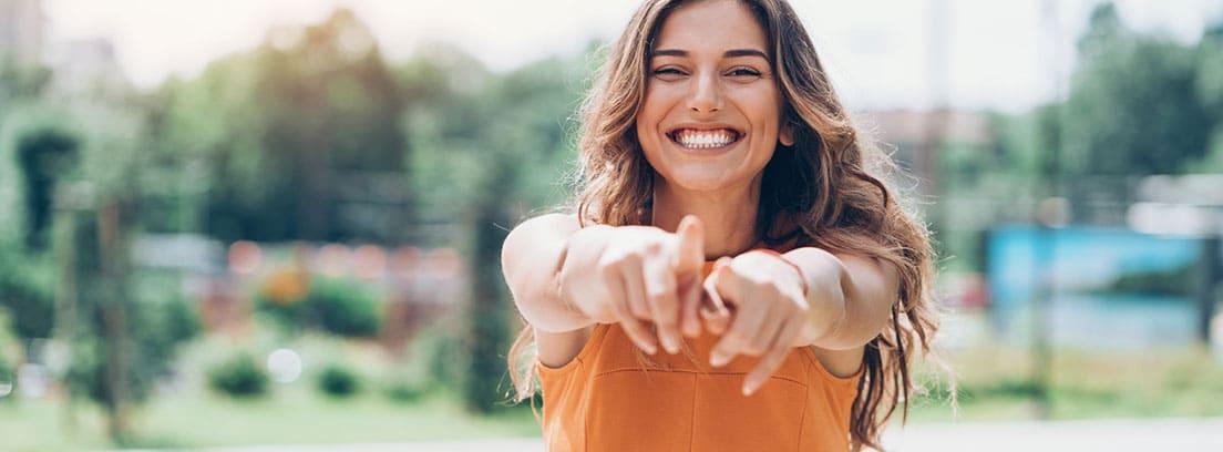 Positivismo vacío: chica joven sonriendo con los brazos extendidos
