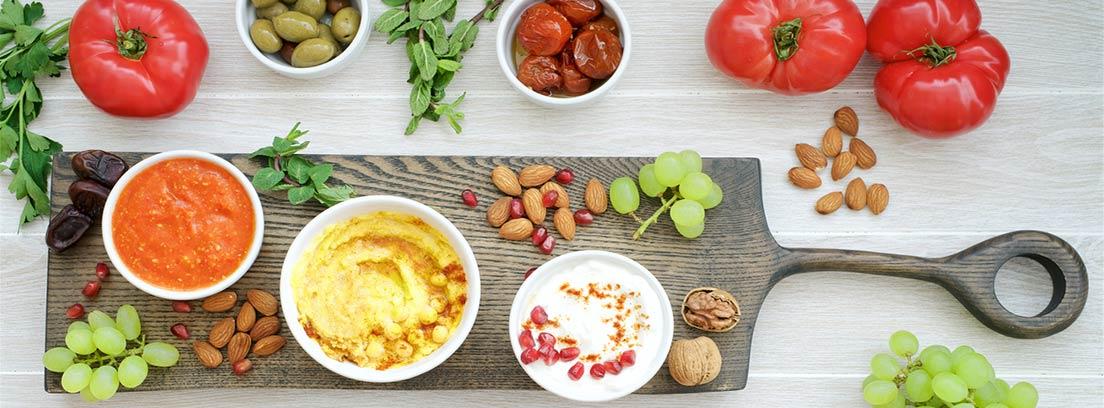 RAW FOOD: Alimentación crudi-vegana: varios vegetales, frutos secos y salsas vegetarianas sobre tabla de madera