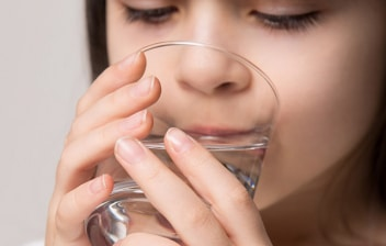Suero oral para combatir la deshidratación en niños : niña bebiendo un baso con suero