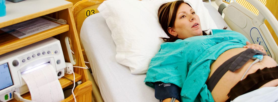 ¿Qué es la monitorización fetal?: mujer embarazada realizándose una prueba de monitorización fetal con el registro de contraccioones