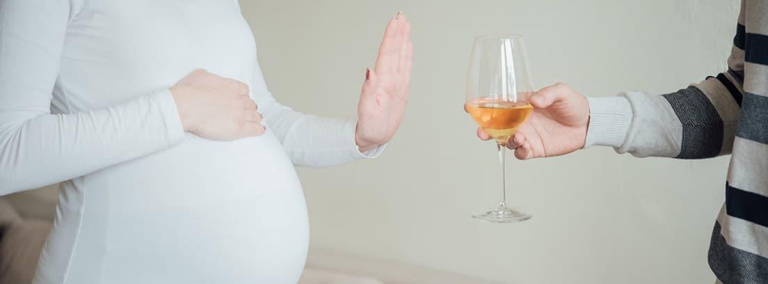 Síndrome alcohólico fetal: mujer embarazada negando con la mano una copa de alcohol