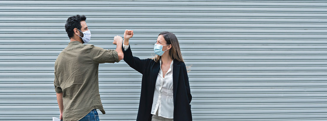 ¿Cómo afecta la nueva normalidad a nuestra salud? : chico y chica con mascarillas saludándose con los codos