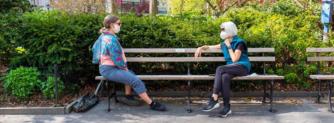 ¿Cómo afecta la nueva normalidad a nuestra salud? : dos mujeres sentadas en un banco de la calle con mascarillas y guardándo la distancia de seguridad