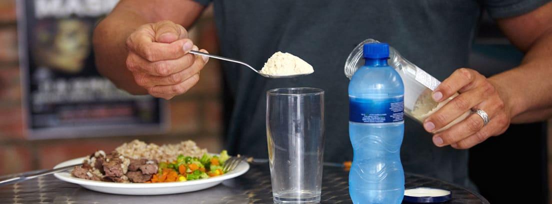 Suplementos deportivos grupo A: hombre añadiendo a un vaso de agua un suplemento alimenticio