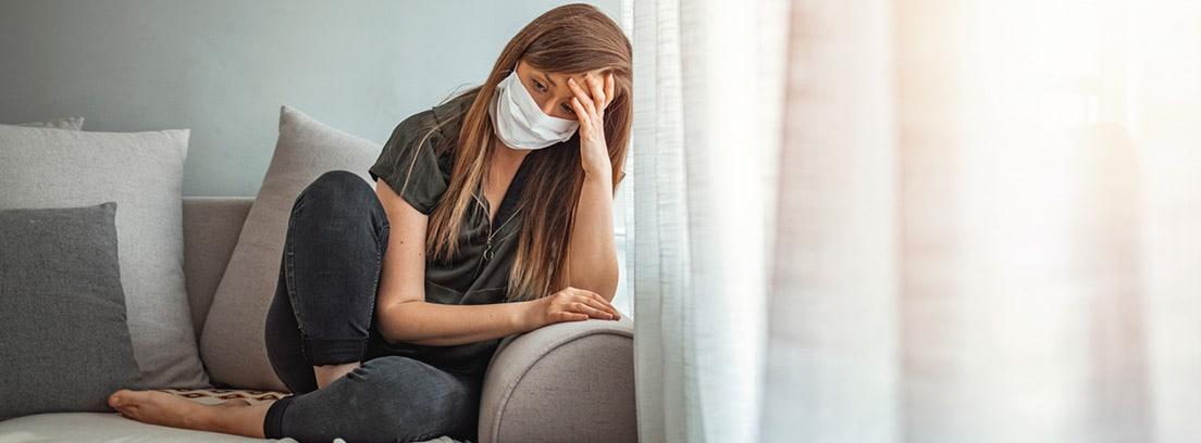 Nuevas conductas sociales tras el COVID 19: chica solitaria en casa con máscara protectora en la cara mirando a la ventana