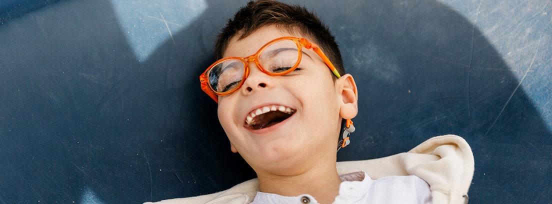 Enfermedad de Leigh: niño riéndose con unas gafas naranjas