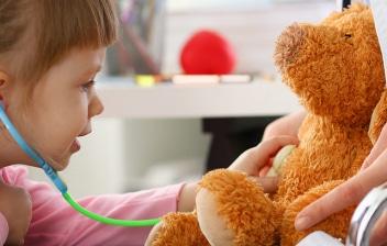 Enfermedad de Leigh: La mano niña con un estetoscopio escuchando el corazón de un oso de peluche en consulta médica