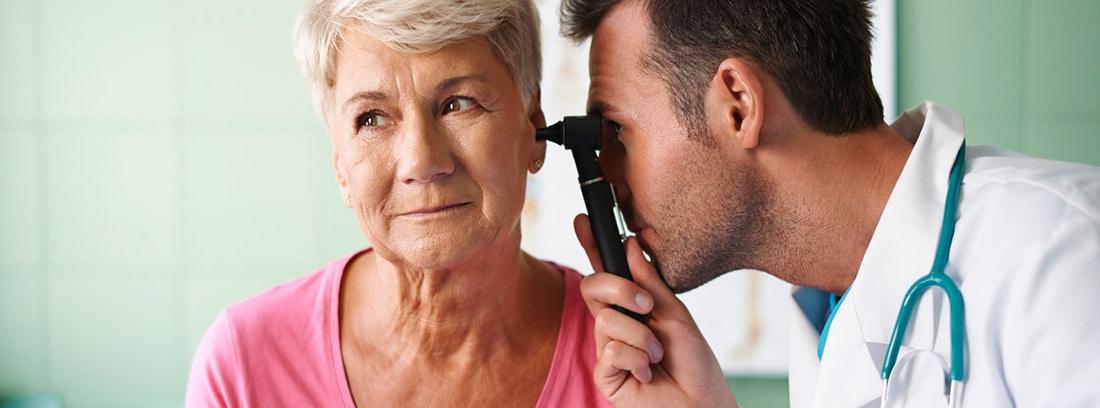 Eliminar los tapones de cera de los oídos:Otorrino revisando el oído de una mujer mayor