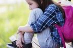 Qué significa tener un retraso madurativo: niña sentada con los brazos rodeando las rodillas y una mochila en la espalda