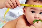 ¿Qué es la macrocefalia?: bebé tumbado boca abajo y médico midiéndole el perímetro cefálico