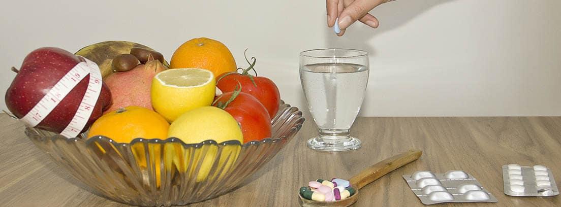 suplementos dietéticos: mano echando un suplemento dietético a una copa con agua y diversas frutas dentro de un recipiente de cristal